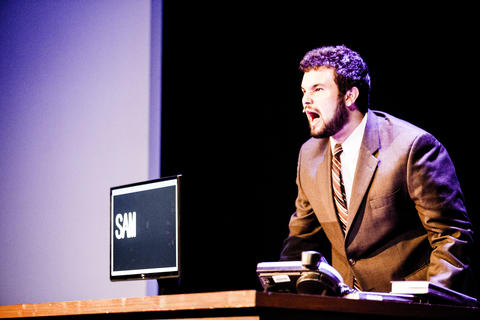 Close-up of male actor beside a computer performing on-stage.