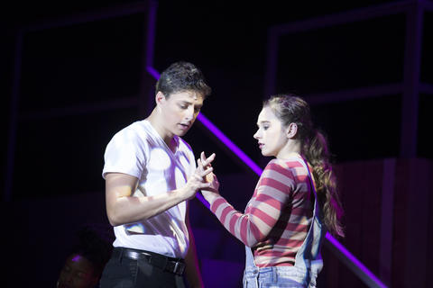 Close-up of male and female dancing together as they perform on-stage.