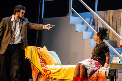 Close-up of male actor pointing gun at Haley Johnson while performing on-stage.