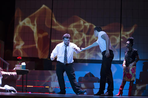 Two male actors performing together on-stage with Haley Johnson in the background and a large screen of orange flames.