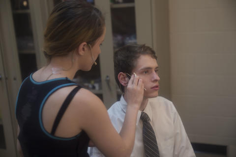 Female make-up artist preps male actor backstage for the performance.