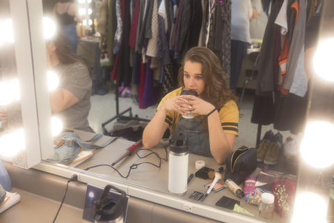 Female actor sips coffee in front of a mirror backstage.