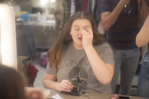 Female actor applies make-up backstage for the performance.
