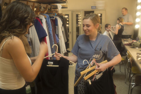 Two female actors sift through clothing backstage to find their costumes.
