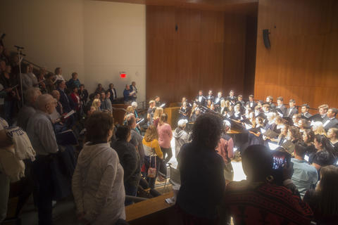 Audience standing and singing with the concert choir