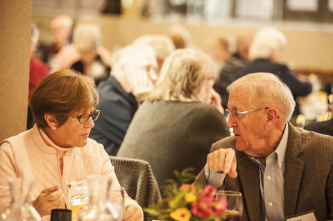 Female and Male Alumnist talking at dinner