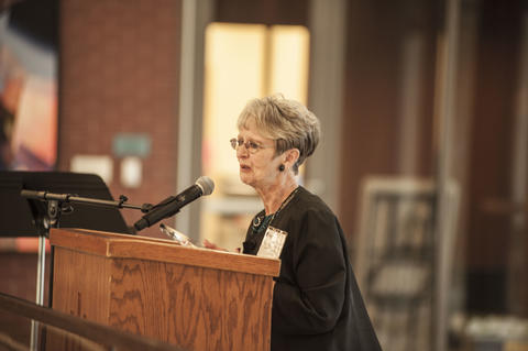 Female Alumnist speaking to crowd