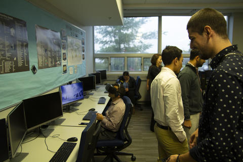 Alumni and current students programing on computers