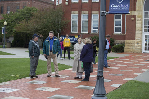 Alumni standing outside of the administration building