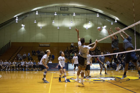 A thunderous spike made by the alumni.