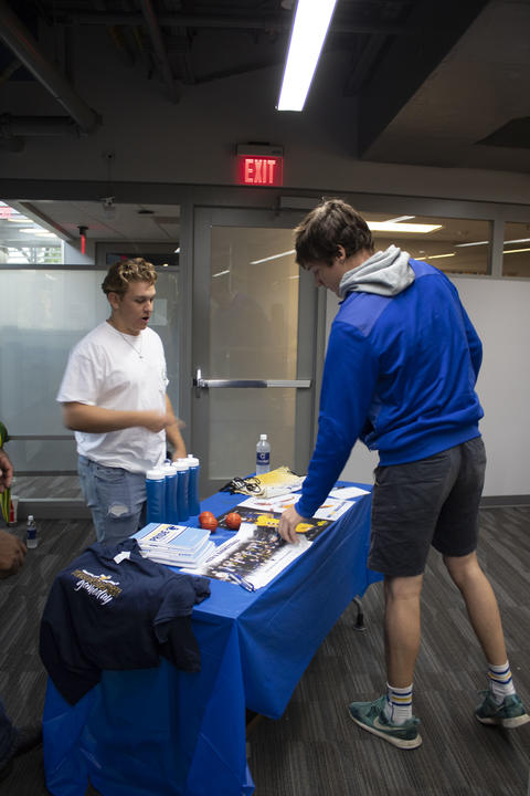 Future Graceland student getting a GU Men's Basketball team poster.