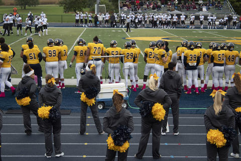Cheer squad and football team looking out at the field