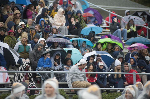 Crowd covering up with umbrellas for the rain storm