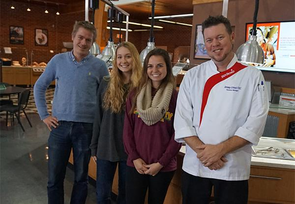Professor Dan Platt, two female students and Sodexo chef pose in the Commons eating hall