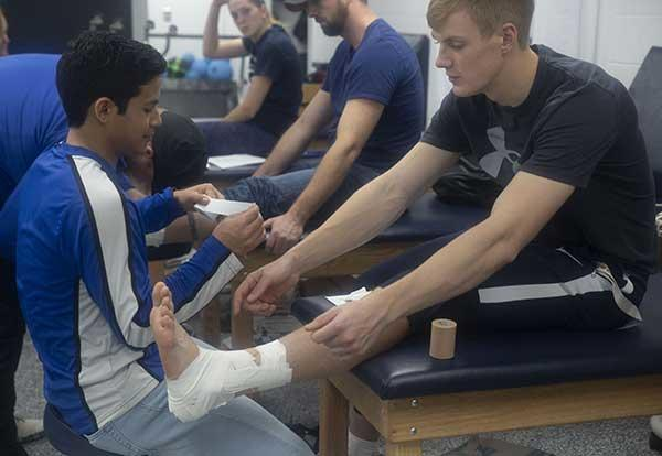 Two male Graceland students practicing ankle wrapping in the athletic training room.