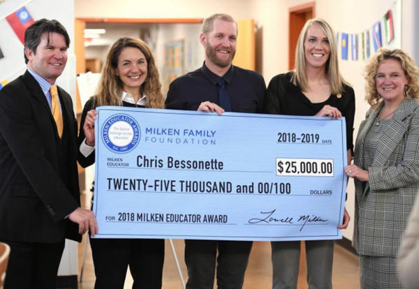Bessonette and others holding oversized check for $25,000.