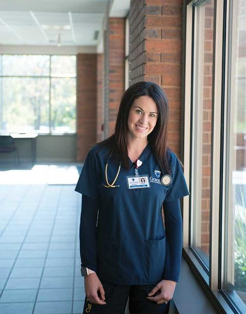 Female nursing student in scrubs poses in front of windows along the hallway of the School of Nursing