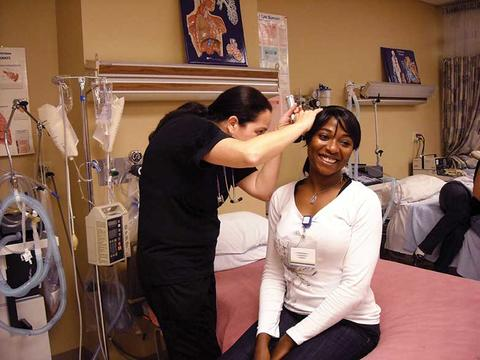 Female nursing student practices technique on another female nursing student acting as patient in a clinical setting