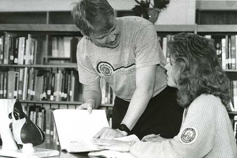 Black and white photos of male professor going through printed materials with a female nursing student