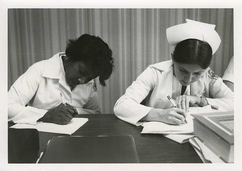 Black and white photo of two nursing students studying their materials in the classroom