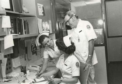 Black and white photo of two female nursing students working through their study materials being overseen by a male nursing professor