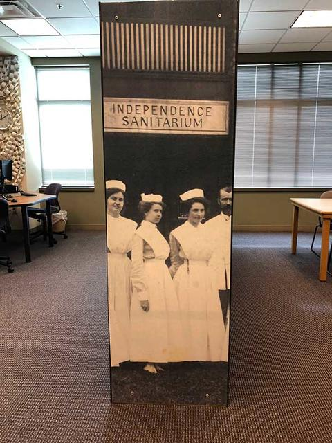 Enlarged black and white photo of nursing students adhered to end cap of bookshelf