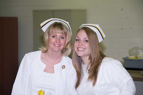 Two female nursing students in white nursing coats and hats from a few years back