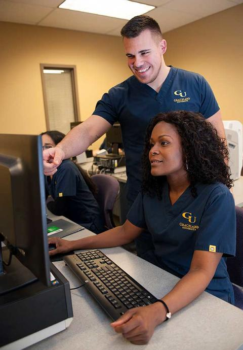 Female nursing student works at computer while professor instructs her