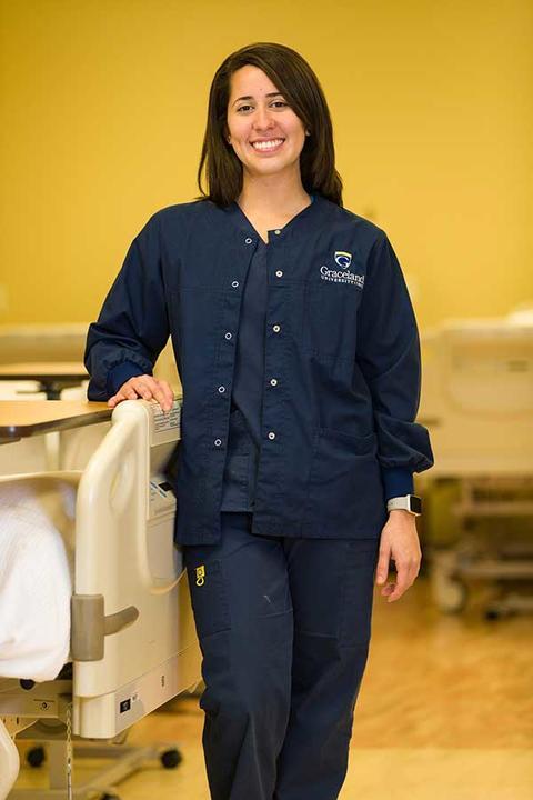 Female nursing student in scrubs poses in nursing simulation room on campus