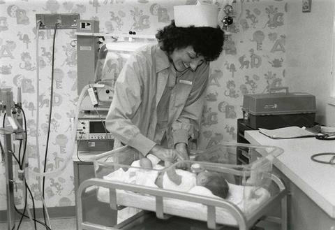 Black and white photo of a nurse taking care of an infant in a nursery