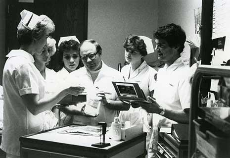Black and white photo of a group of nursing student in uniform gathered going over procedure in the early days of the nursing program