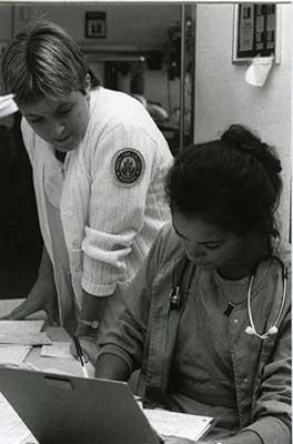 Black and white older photo of a female nursing professor guiding a female nursing student through study materials