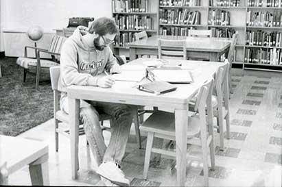 Black and white photo of male nursing student in the library at a table studying
