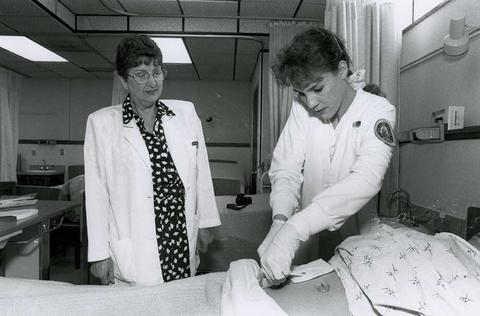 Black and white female nursing student works on a patient in a clinical setting with her nursing professor overseeing