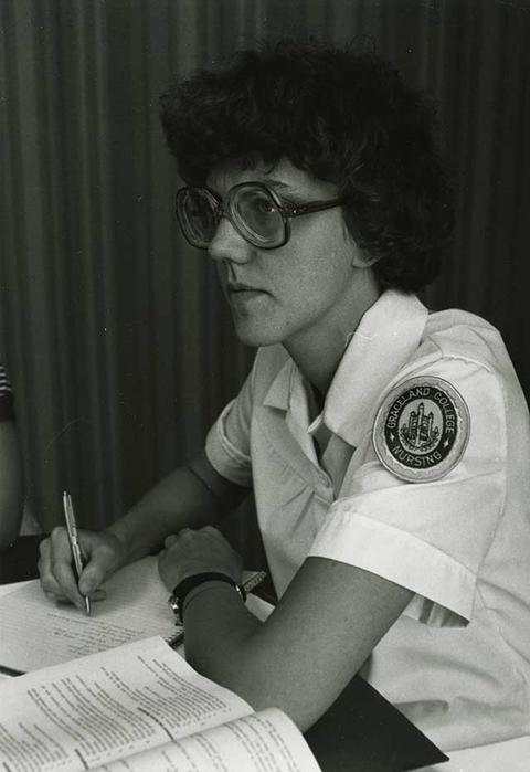 Black and white photo of a female nursing student studying