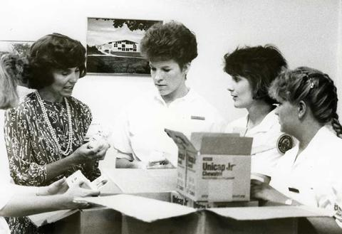 Black and white photo of nursing professor demonstrating to three nursing students