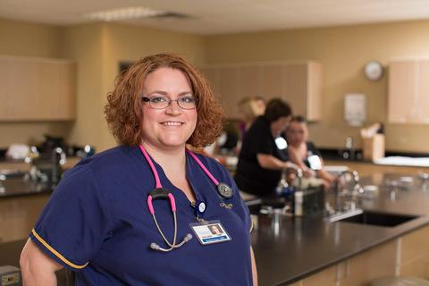 Female nursing student in navy scrubs with stethoscope in a clinical setting