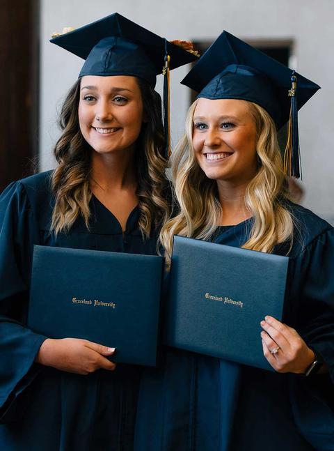 Two female nursing graduates in regalia and holding their diplomas