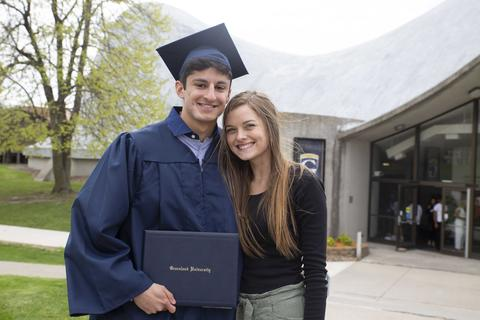 Gerardo poses in his cap and gown, holding his diploma, with his girlfriend outside Closson following commencement