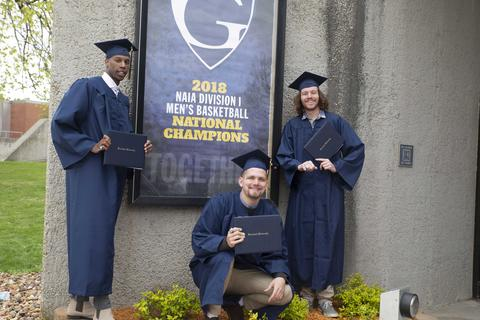 Three male graduates in their regalia pose with their diplomas outside Closson in front of a large, framed Graceland logo poster following commencement.