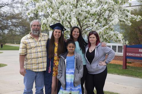 Female graduate in regalia poses with her family outside in front of a beautifully blooming tree of white flowers on campus.