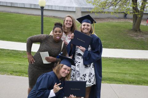 Two female graduates in cap and gown with their diplomas pose with two other female students outside Closson following commencement.
