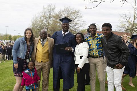 International student Evaristo Casimiro poses with his family in his regalia following commencement