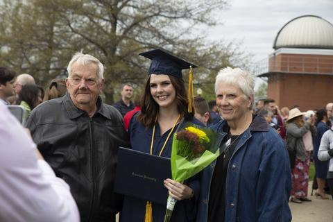 Female graduate in cap and gown holding her diploma poses with her grandparents outside Closson