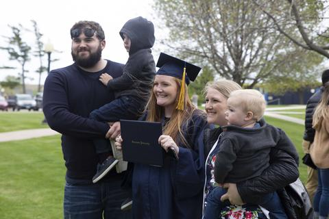 Family members with young children pose with female graduate in regalia following commencement