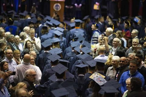 Overhead image of two rows of graduating students' caps as they file down the aisle through the audience to be seated