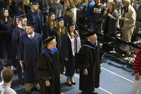 Two faculty lead the two rows of graduates in their regalia down the aisle at commencement