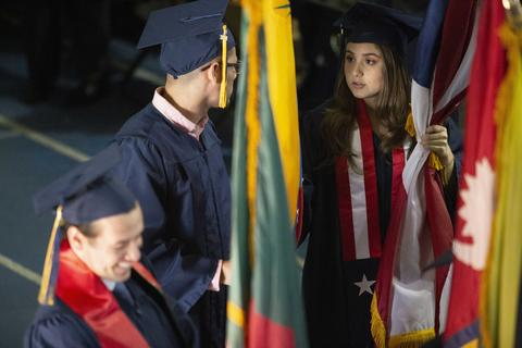 International students in cap and gown carrying their country's flags down the aisle for commencement