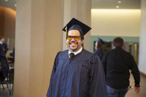 Male graduate smiling hugely in cap and gown in Shaw Lobby