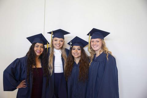 Four female graduates pose together in the Shaw Lobby in their graduation regalia
